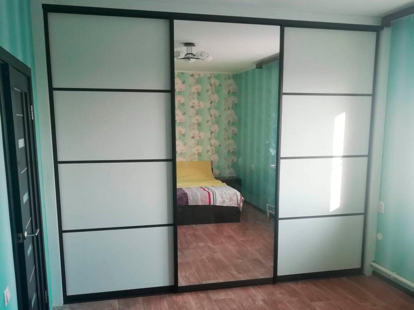 Встроенная гардеробная из ЛДСП вдоль стены комнаты